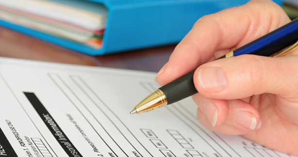 image of hand filling out a form