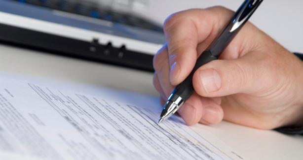 photo of hand holding pen and filling out a form
