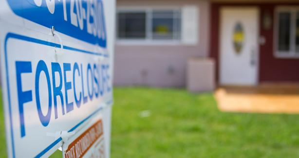 photo of a front yard of a house with a foreclosure sign