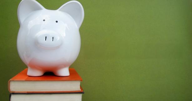 photo of a piggy bank atop a stack of books
