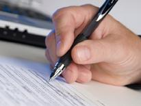 photo of hand holding pen and filling out a form1