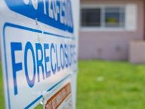 photograph of a foreclosure sign in front of a house